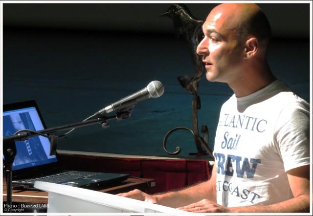 """Frankalone, nom d'artiste de Franck Bibia, lors du colloque du 1er juin au théâtre Georges-Galli: ci dessous un extrait de son intervention lorsqu'il vient d'offrir au musée lma sculture Le dauphin au trois volutes"""" acier ."""